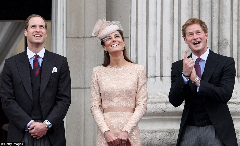 Prince William, Kate and Harry stand smiling on the balcony of Buckingham Palace as they watch the RAF flypast