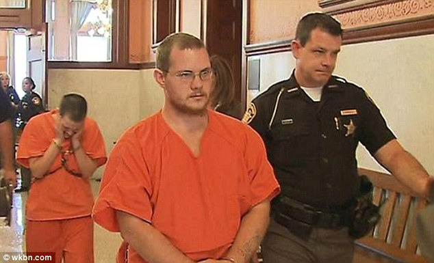Shackled: Cody, front, and Felicia Beemer, behind, are led into court in their orange prison suits and chains