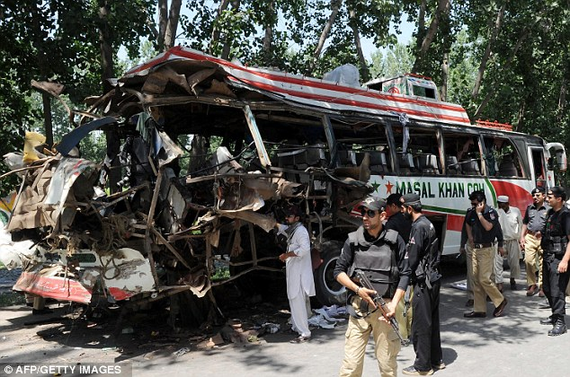 Carnage: Pakistani security officials examine the wreckage of the destroyed bus on the outskirts of Peshawar
