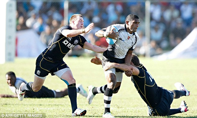 No way through: Fiji's half back Nikola Matawalu (centre) is tackled by Scotland's players