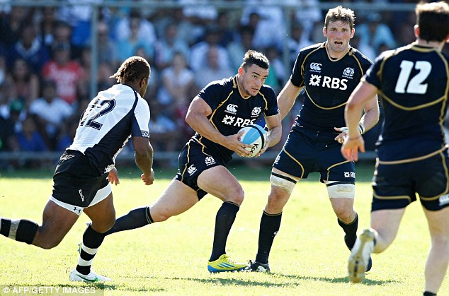 Winning feeling: Scotland's hooker Max Evans (centre) charges forward against Fiji