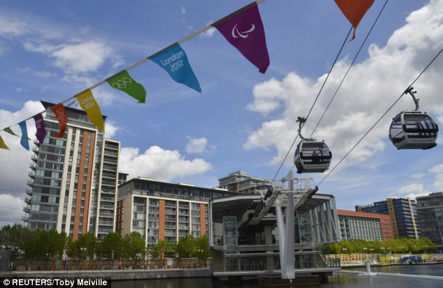 Workers sit in gondolas as they perform tests on the new cable car link across the River Thames in London earlier today