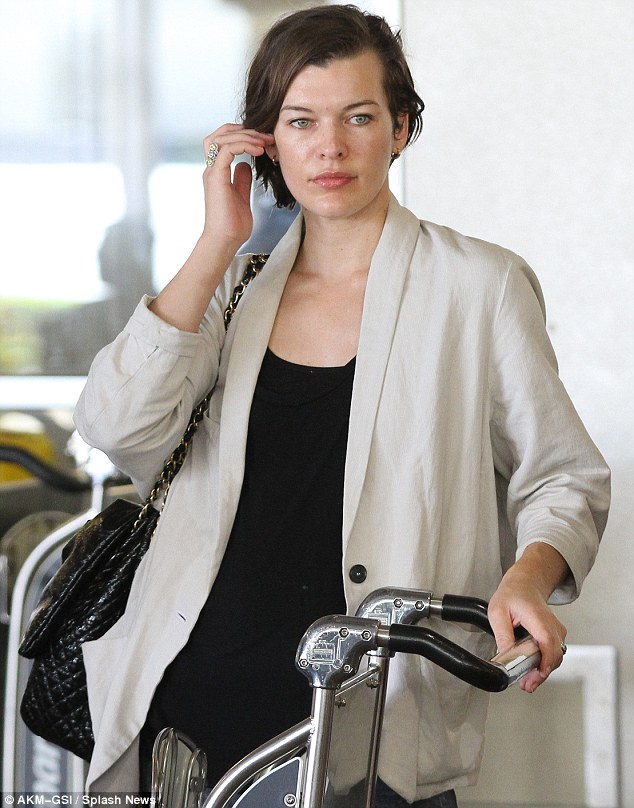 Fresh faced and fabulous: Milla Jovovich still looked stunning with ho make-up as she arrived at LAX with her family today