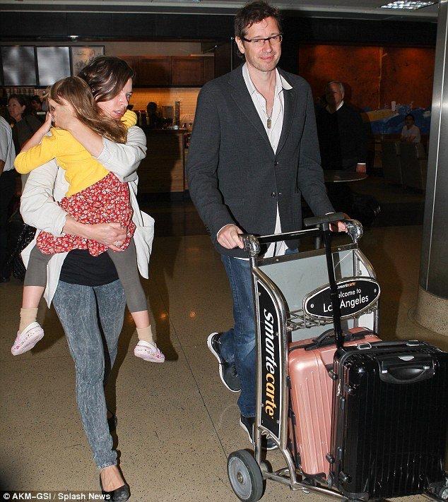 Weary: Milla carried her tired and growing little girl Ever through the terminal, while husband Paul WS Anderson wheeled their luggage cart