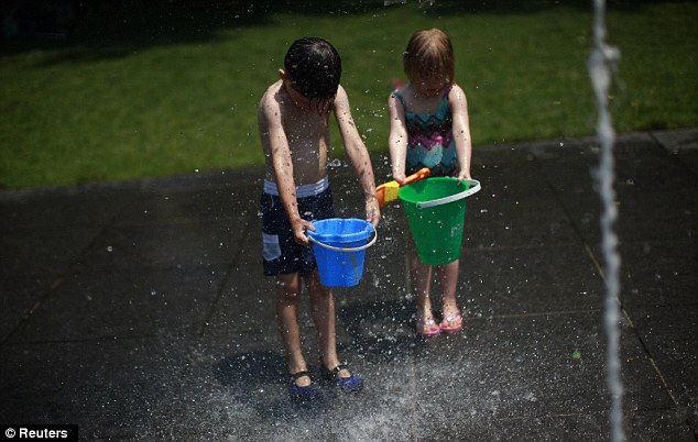 Day out: Children cool down at a fountain in New York City on Wednesday