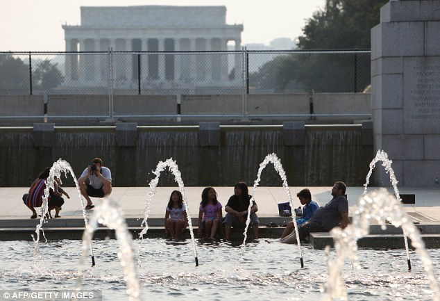 Water: People refresh themselves at the WWII memorial in Washington