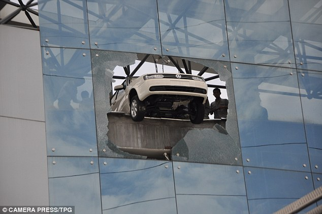 The saloon car was left dangling precariously from the high-rise car showroom in Liuzhou, China