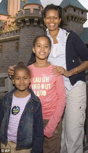 Holiday fun: Malia (middle) at age eight in Disneyland, with Sasha, 5, and Michelle Obama