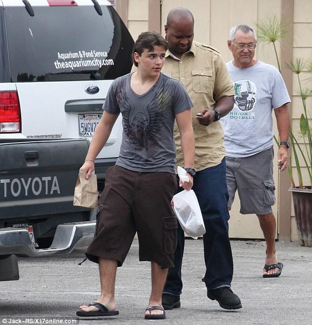Blossoming: O adolescente mostrou um pouco de personalidade em uma camisa cinza impresso de uma águia e shorts de carga