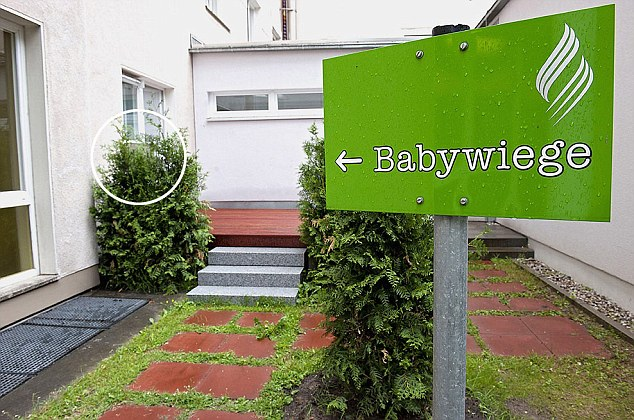 Sad direction: The sign pointing to the baby box (circle), which is virtually obscured by shrubbery