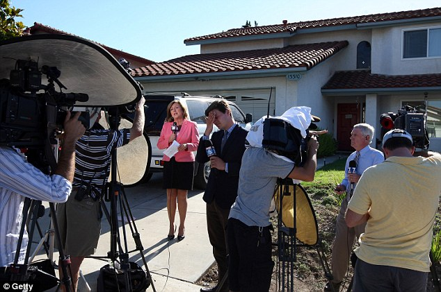 Television news crews set up for their live reports in front of the home of Robert and Arlene Homes, parents of James