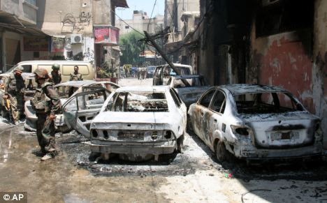 In this photo taken during a government-organized tour, Syrian soldiers stand next to burned cars after they regained control of the district of Midan, in the southern part of Damascus, Syria, on Friday