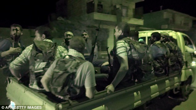 Unrest: This image allegedly shows newly recruited members of the Free Syrian Army riding on the back of a pick-up truck in Aleppo