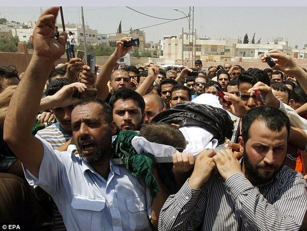 Innocent victim: The body of a four-year old Syrian boy who was shot while fleeing the country with his family to Jordan is carried during his funeral service in Ramtha, Jordan, today