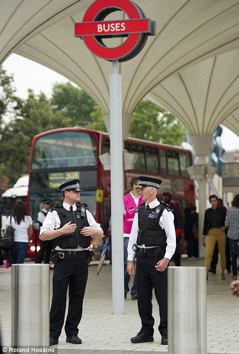 Two officers stand guard outside a bus station in Stratford where thousands of people will be arriving throughout the course of the evening