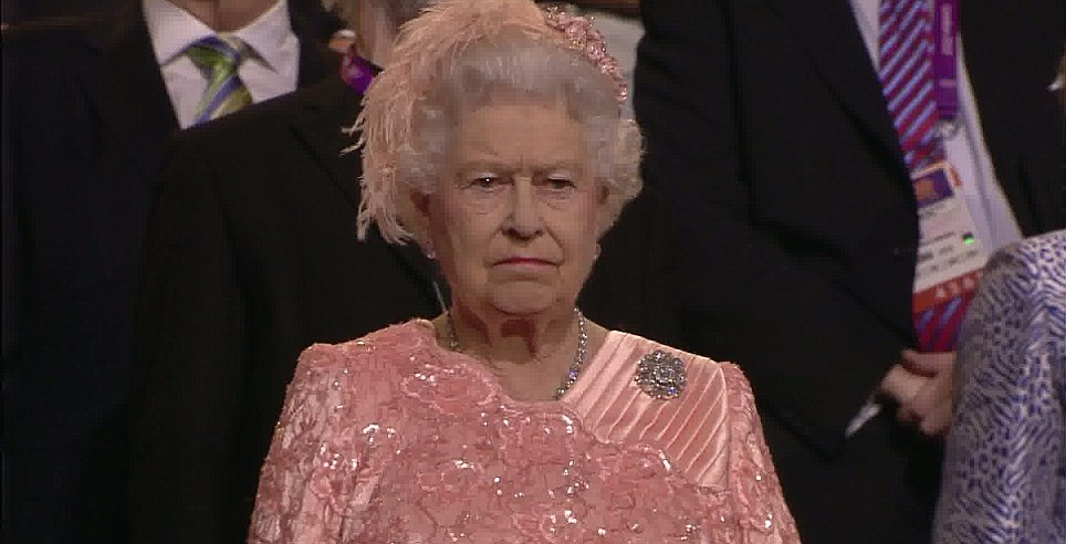 After appearing in the stadium, looking dishevelled, a disgruntled-looking Queen adjusts herself and then takes her seat in the VIP area