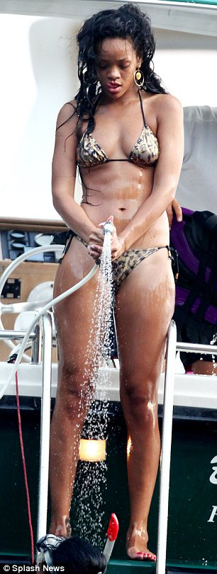 Cooling down: The singer soaked herself with a hose after taking a dip in the sea off the coast of Portofino in Italy