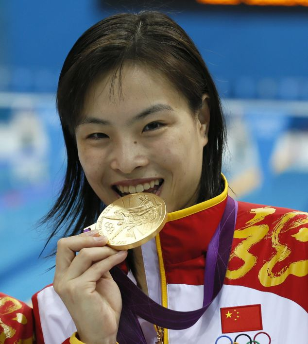 Tinged with sadness: Minxia Wu of China celebrates her gold medal in women's Synchronised 3m Springboard. She was then told the devastating secret