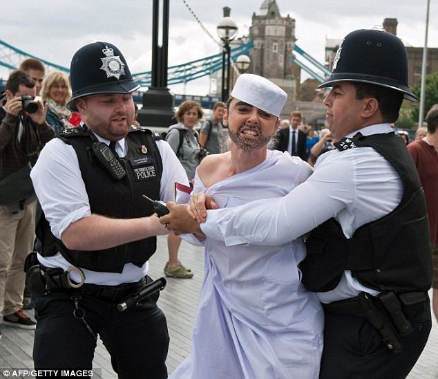 COPPER ON THE LEFT CANT HELP CHUCKLE AS HE HAD A QUICK LOOK AT HER BOOBS.BEST LOOKING MUSLIM IV EVER SEEN.Interest: Onlookers take photographs as two police officers block a woman dressed as a Muslim man