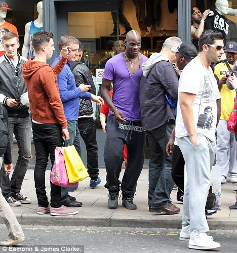 Mobbed: Mario Balotelli's presence at a shop in Manchester caused such chaotic scenes that the store had to close so he could shop without being mobbed