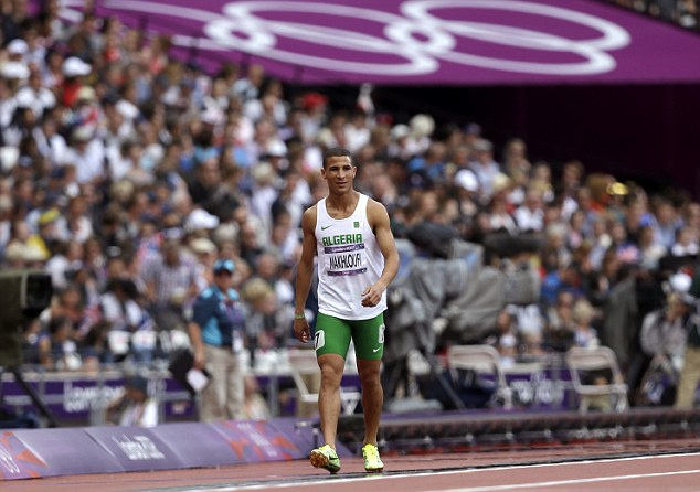Not trying hard enough: Algeria's Taoufik Makhloufi casually strolls off the track after giving up during his 800m heat on Monday