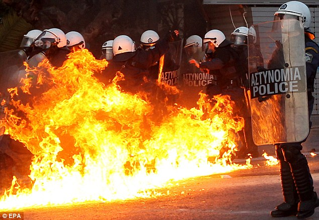 Protesters clash with riot police outside of the Greek Parliament in Athens, in February