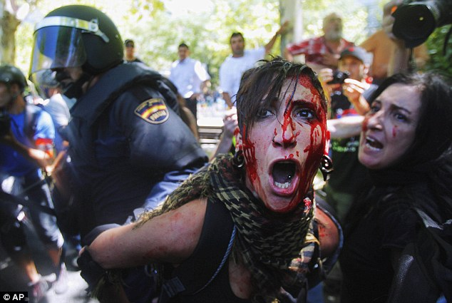 A bleeding protester is led away by riot police during a rally in the Spanish capital