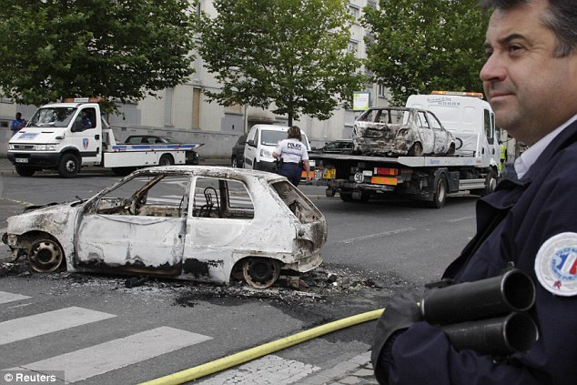 Aftermath: A police officer stands guard near cars destroyed in the overnight clashes