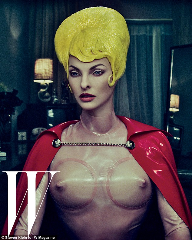 Plastic fantastic: The former supermodel - now 47 - stares blankly while modelling fake breasts , worn with a red cape and plastic yellow wig