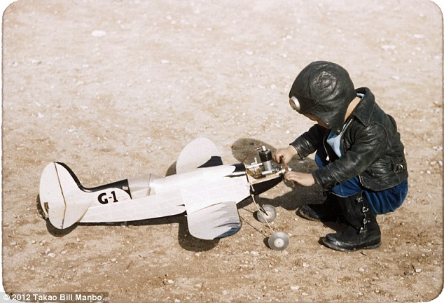 Billy Manbo, in pilot attire, plays with a model airplane. Photo by Bill Manbo