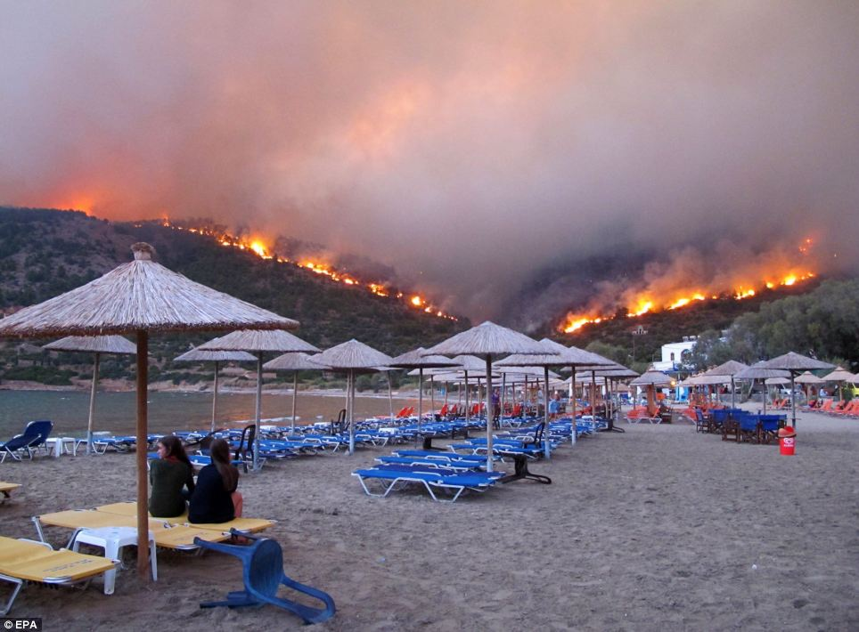 All-consuming: Two girls are sat at the beach watching the roaring fire destroy the forests on the mountains as it move closed to the beach where evacuees from nearby villages have gathered