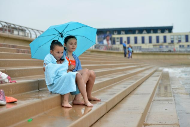 What to expect: Demi, nine, and Chelsea Brookes, 11, sit in the rain on Blackpool Beach. Forecasters say this is what's in store for the bank holiday weekend