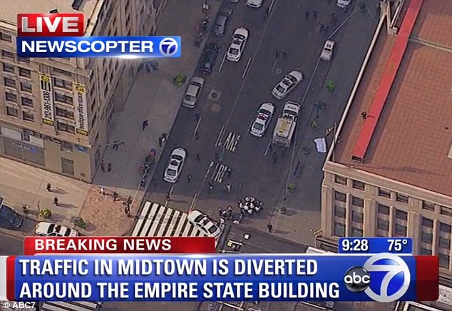 Chaos: Four people have been shot by a gunman outside the Empire State Building. A helicopter shot shows the scene moments after the shooting, with one victim covered by a sheet, right