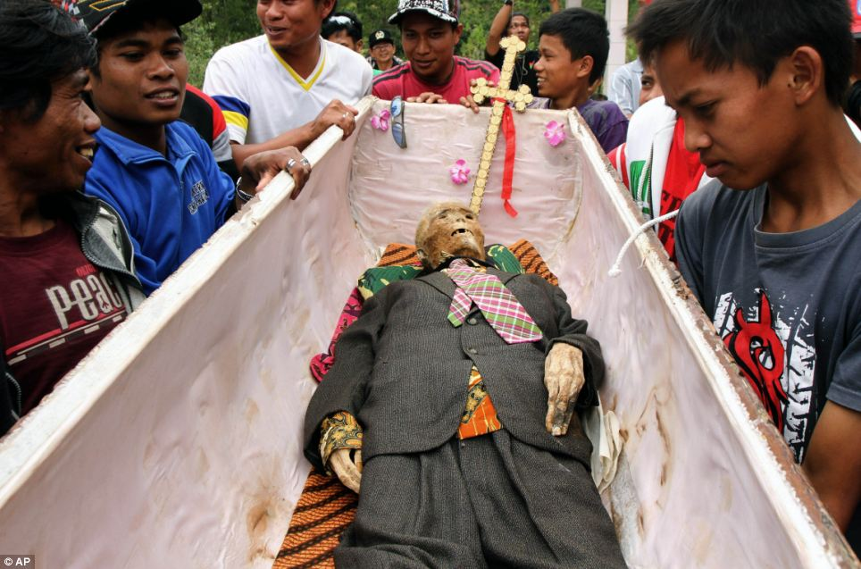 Dressing down: Family members carry a coffin containing the preserved body of their relative after putting a new set of clothing on it