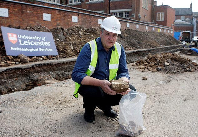Richard Buckley holding a piece of mullion from a traceried window from the later medieval period at the archaeological site in Leicester