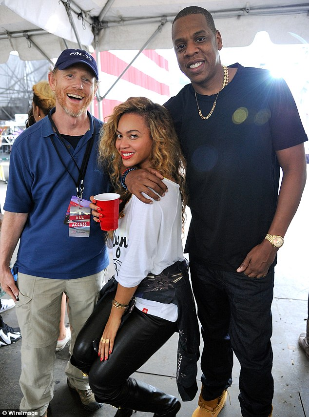 Cute couple: Jay-Z put his arm affectionately around his wife as they posed with Director Ron Howard
