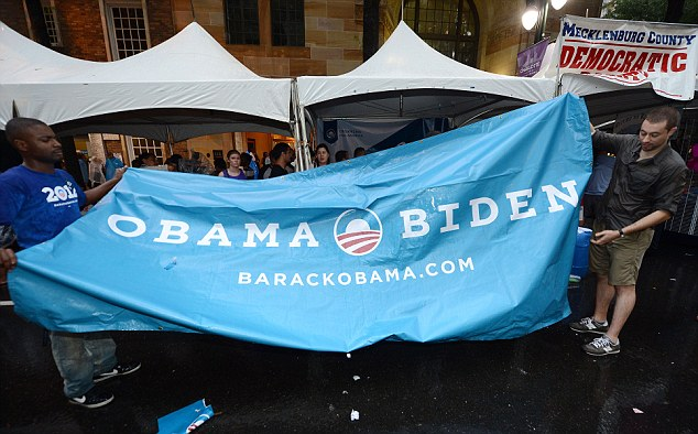 Campaign workers fold up an Obama banner after a sudden thunderstorm washed out the Carolina Fest street fair, in Charlotte, North Carolina