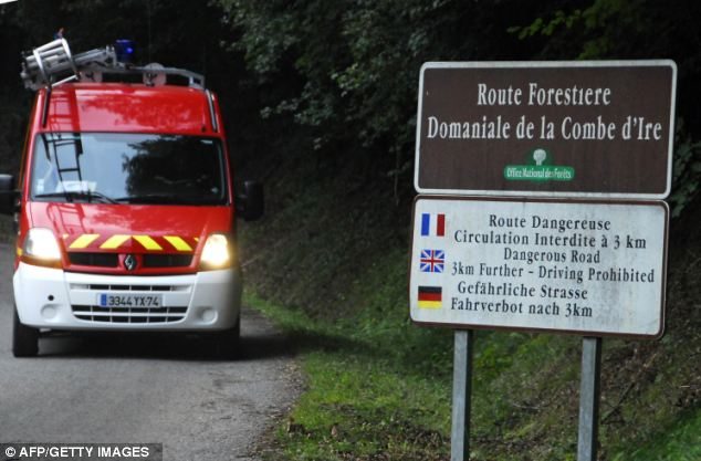 Closed off: A firemen and rescue vehicle is driven on the road leading to the grisly scene