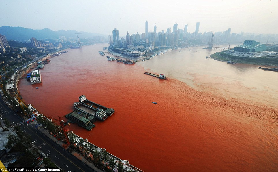 Meeting point: A ship sails across the junction of the polluted Yangtze River (left) and the Jialin River in Chongqing, China, yesterday