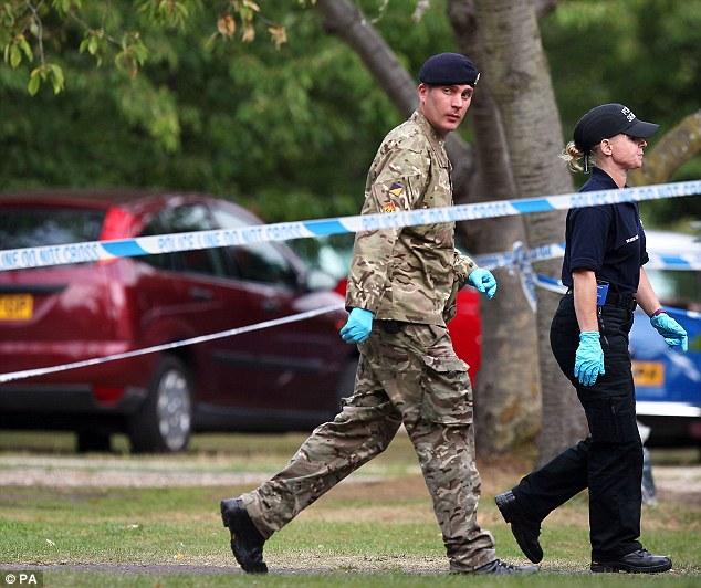 Un miembro del equipo de Royal Logistic Corps disposición bomba camina con un cierre oficial de la policía a la casa de Saad al-Hilli en Claygate, Surrey mientras se profundiza la investigación