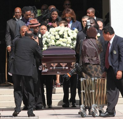 Tragic: Omarosa was seen crying as the coffin was being carried with a large garland of flowers upon it