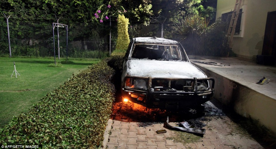 Destruction: A burned-out car smoulders at the scene. It is unclear if this vehicle was used by Ambassador Stevens and his team as he attempted to escape