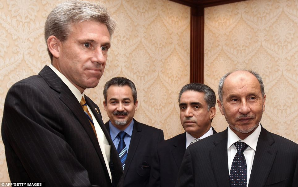 Reported dead: John Christopher Stevens, left, US ambassador to Libya, shakes hands with Libyan National Transitional Council chairman Mustafa Abdel Jalil (right) during a meeting in Tripoli on June 7, 2012
