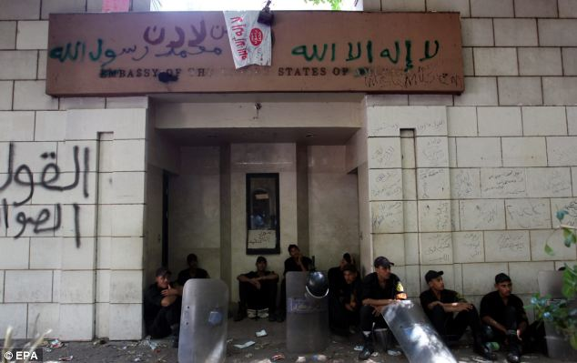 Protection: Egyptian soldiers sit at one entrance to the US embassy, one day after Islamist protesters scaled the walls of the embassy in Cairo