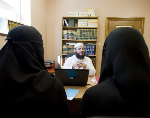 Influential: An imam advises two women at Leytonstone Islamic Centre, in east London