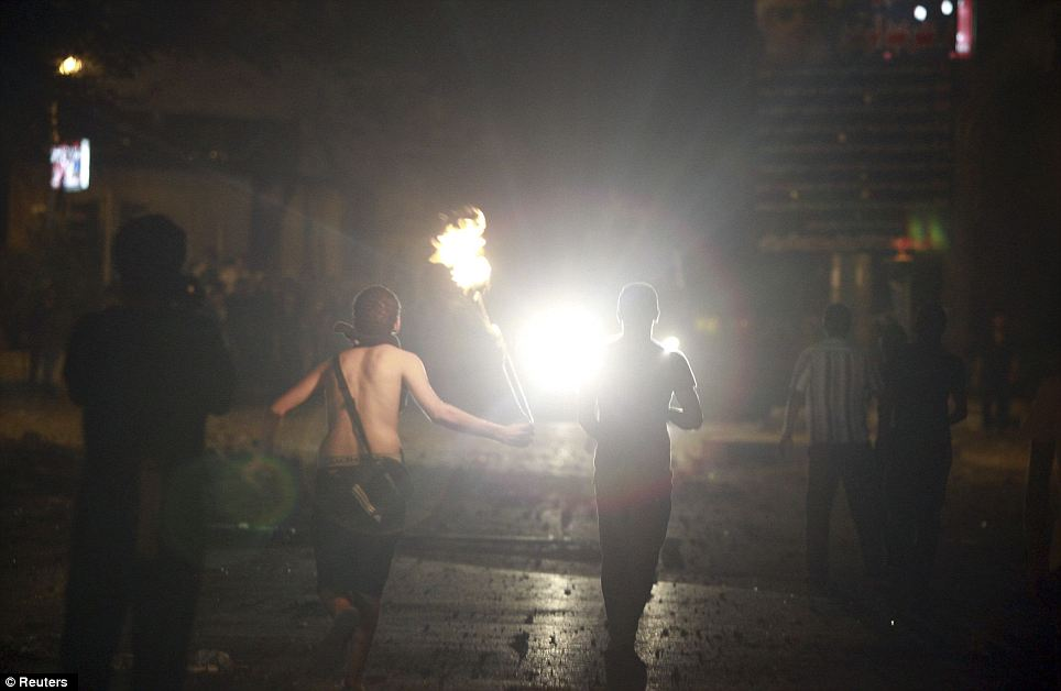 Riots: A protester throws a petrol bomb at policemen during clashes along a road which leads to the U.S. embassy, near Tahrir Square in Cairo on Wednesday night