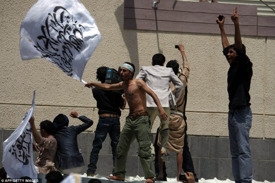 Mass fury: A Yemeni protester waves the flag as thousands of people gather at the main gate of the mission