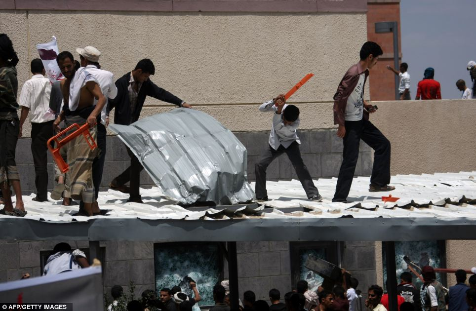 Dramatic: The demonstrators try to break into the embassy by tearing up the roof and pounding it with makeshift weapons