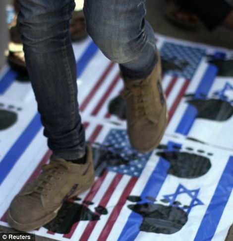 others walk on U.S. and Israeli national flags