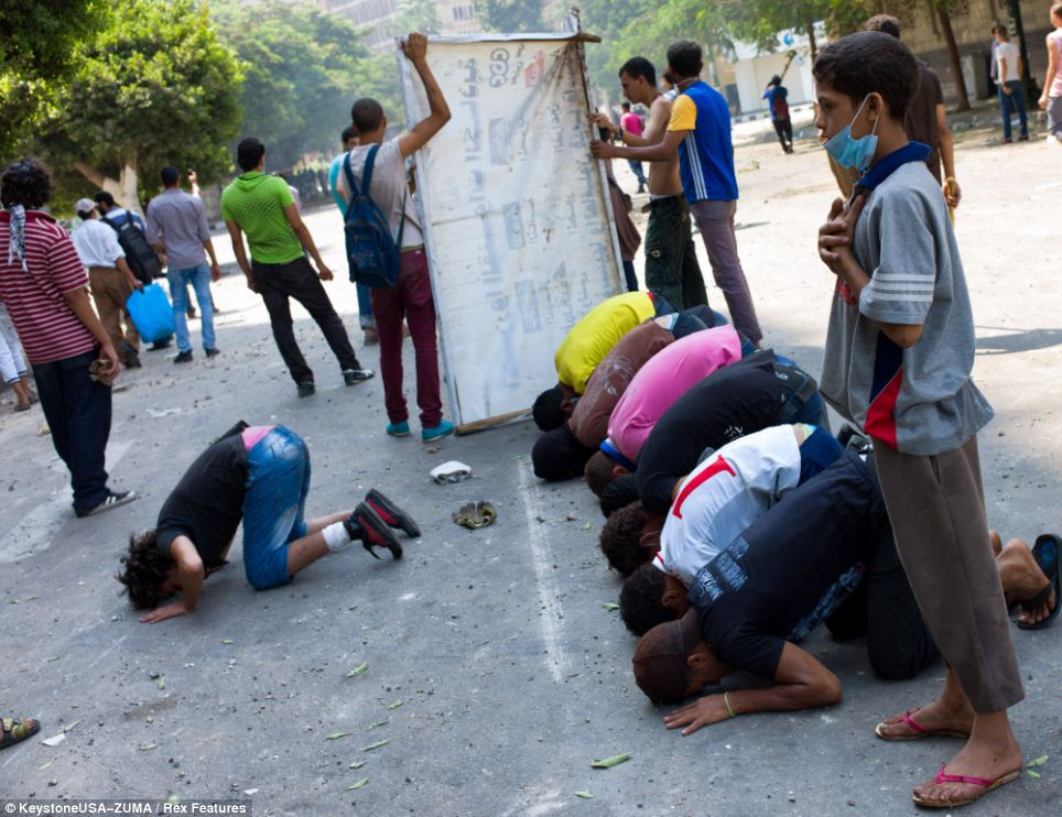 Waiting for help: Protesters pray during clashes with police in a street leading to Tahrir square